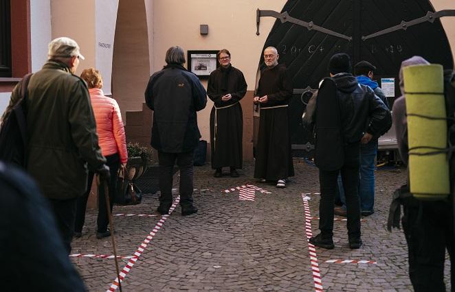 Br. Paulus und Br. Michael begrüßen Obdachlose vor dem Franziskustreff